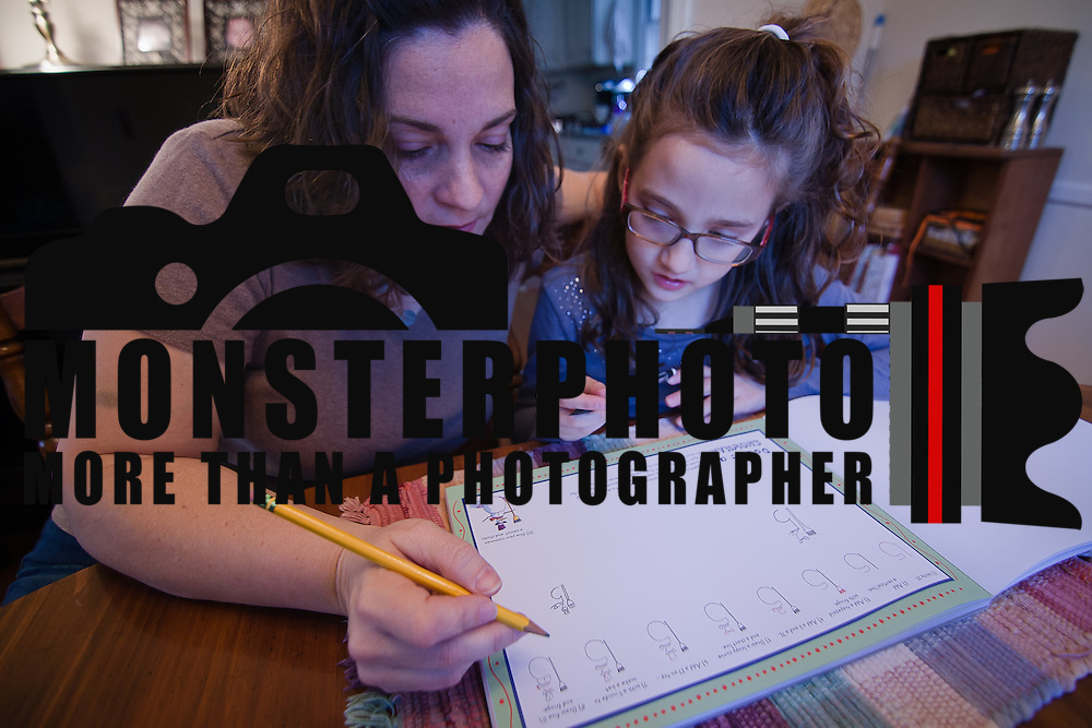 02/03/12 Newark DE: Elisa Cottrell (Left) and daughter Cason Cottrell (9) (Right) work on homework together at the dining room table in their home Friday, Feb. 3, 2012 in Newark Delaware...Special to The News Journal/SAQUAN STIMPSON