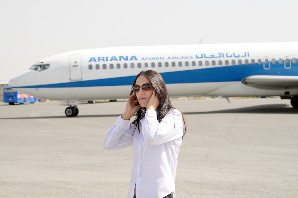 "Pilot, Danielle Aitchison, covers her ears while an Ariana Afghan Airlines Boeing 727 taxis for takeoff at Kabul International Airport.  Danielle flies in Afghanistan for The United Nations Humanitarian Air Service (UNHAS).   ...When asked about flying in a war zone, she says,  ""I'm just a normal average female.  My job is maybe a little different to some, but I have the same feminine side as other women.  I don't have any trouble going back to New Zealand relating to people.  I'm just a regular chick.""."