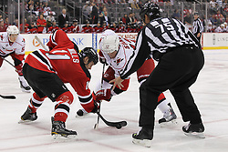 Oct 10; Newark, NJ, USA; New Jersey Devils center Brad Mills (11) and Carolina Hurricanes center Eric Staal (12) face off during the first period at the Prudential Center.