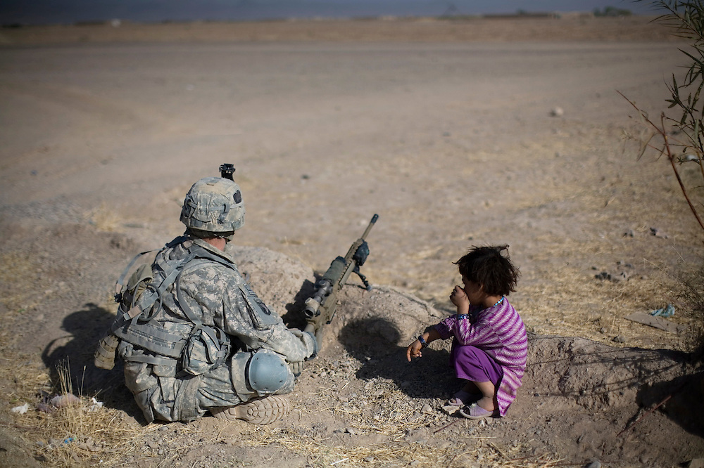 A US Army soldier from Scout Platoon 2nd Battalion, 502 Infantry Regiment, 101st Airborne Division, keeps watch next to an Afghan girl near an outpost in Zhari district, Kandahar province, Saturday, Oct. 9, 2010.  The Scouts' mission was to support roadside bomb clearance efforts in the militant stronghold, the latest days-long phase of Operation Dragon Strike. (AP Photo/Rodrigo Abd)