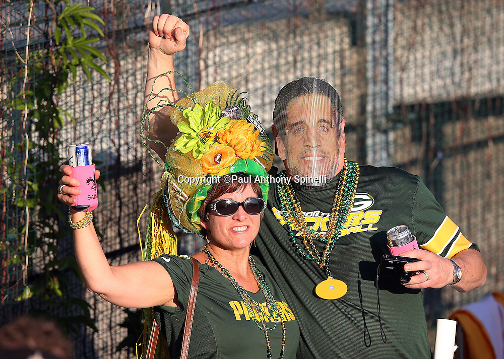 Green Bay Packers fans wear team colored gear and an Packers quarterback Aaron Rodgers (12) face cutout as they get fired up for the Green Bay Packers NFL week 8 regular season football game against the New Orleans Saints on Sunday, Oct. 26, 2014 in New Orleans. The Saints won the game 44-23. ©Paul Anthony Spinelli