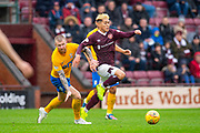 Ryotaro Meshino (#77) of Heart of Midlothian FC skips past Alan Power (#6) of Kilmarnock FC during the Ladbrokes Scottish Premiership match between Heart of Midlothian FC and Kilmarnock FC at Tynecastle Park, Edinburgh, Scotland on 5 October 2019.