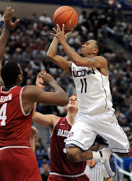Connecticut's Ryan Boatright, right, goes up for a basket while guarded by Arkansas' Devonta Abron, left, and Michael Sanchez , back center  in the second half of an NCAA college basketball game in Hartford, Conn., Saturday, Dec. 3, 2011.  Boatright was top scorer for UConn with 23 points as Connecticut defeated Arkansas 75-62.  (AP Photo/Jessica Hill)