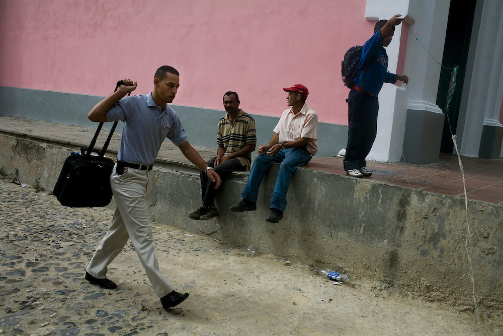 Julio Rodriguez, a sales rep for Pfizer, walks through the streets of Petare, one of the largest and most dangerous slums of Caracas, on his way to a sales call. Pfizer is trying to increase their market share in the slums and are targeting clinics, hospitals and pharmacies, sending sales representatives to the far reaches of the slum.