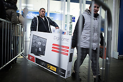 © Licensed to London News Pictures . 27/11/2015 . Salford , UK . Two people carrying two televisions from a branch of Tesco in Pendleton , Salford , this morning (Friday 27th November) as people behind queue for Black Friday offers . Last year (2014) scuffles and fights were reported amongst queuing bargain-hunters . Photo credit: Joel Goodman/LNP