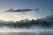 The summit of Whiteface Mountain reaches above the foggy waters of Franklin Falls Pond just before sunrise in the Adirondacks of New York.