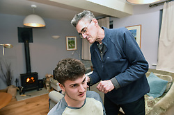 Life in coronavirus lockdown in the UK April 2020. Father cutting his son's hair using clippers.  Model released.