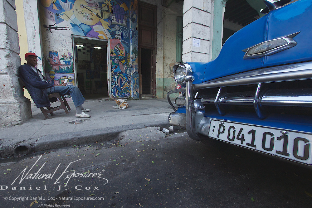 A gallery owner on the sidewalk outside his who in Havana, Cuba.