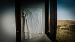 painting covered by a sheet in a house by the ocean