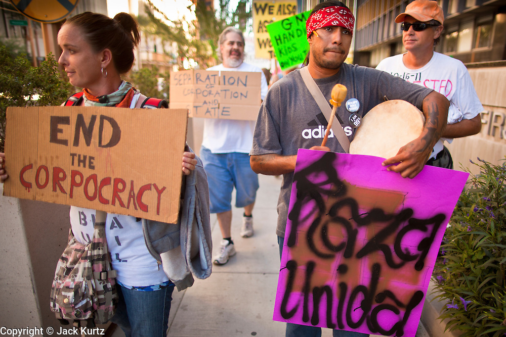 """22 OCTOBER 2011 - PHOENIX, AZ:    Occupy Phoenix protesters march through downtown Phoenix Saturday. The demonstrations at Occupy Phoenix, AZ, entered their second week Saturday. About 50 people are staying in Cesar Chavez Plaza, in the heart of downtown. The crowd grows in the evening and on weekends. Protesters have coordinated their actions with police and have gotten permission from the city to set up shade shelters and sleep in the park, but without tents or sleeping bags, which is considered """"urban camping,"""" instead protesters are sleeping on the sidewalk. PHOTO BY JACK KURTZ"""