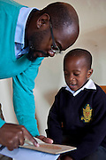 A young African school boy reads green numbers that he can read on an orange plate in a book shown to him by a male optician in a classroom in Zonnebloem School, Cape Town, South Africa.  The book is called the Ishara eye test and is a basic check for colour-blind.  The optician works for Mullers, who volunteer their staff to visit schools and perform eye tests on all children in school grade 2.