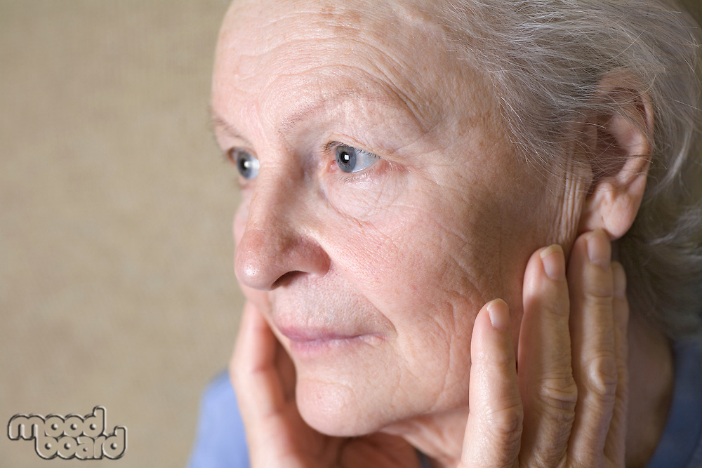 Old lady with her hands to either side of her face  gazing to the side