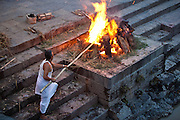 One of the employees at the Pashupatinath Temple in Kathmandu lights the fire ready to burn the bodies for Cremation.