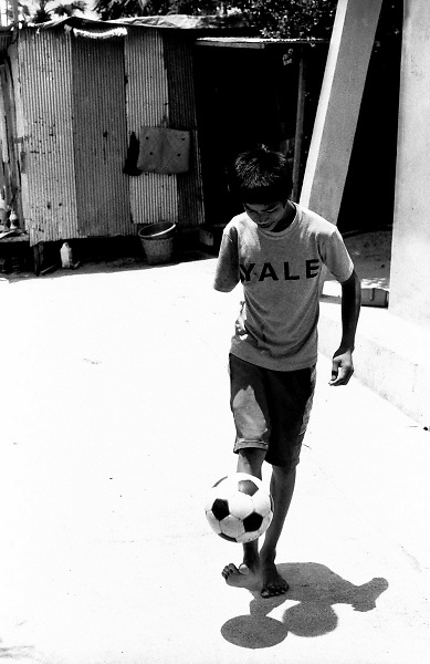 Pheakdei, a landmine survivor, playing football in the courtyard of the Cambodian Landmine Museum in the Siem Reap's province, Cambobia. This boy lost one arm in a active landmine while playing outside his school.