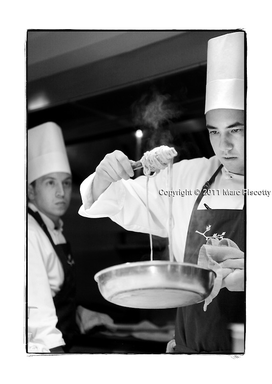 SHOT 1/11/11 7:19:53 PM - Frasca Food and Wine chef Elliot Bernardo (right) prepares to plate a pasta dish as Merick Devine (left) cooks in the background at the Boulder, Co. restaurant. Frasca is a highly-rated neighborhood restaurant inspired by the cuisine and culture of Friuli, Italy. Historically found throughout Friuli, Frascas were friendly and informal gathering places, a destination for farmers, friends, and families to share a meal and a bottle of wine. Identified by a tree branch hanging over a doorway portal, they were a symbol of local farm cuisine, wine, and warm hospitality. (Photo by Marc Piscotty / © 2011)