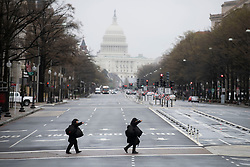 March 24, 2020, Washington, District of Columbia, USA: Two pedestrians walk on a nearly empty street. U.S. Vice President Pence said on Monday that 313,000 coronavirus tests have been completed in the United States, and more than 41,000 tests were positive. (Credit Image: © Xinhua via ZUMA Wire)