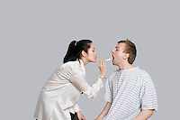 Female doctor examines patient's throat