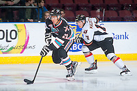 KELOWNA, CANADA - OCTOBER 24: Devante Stephens #21 of Kelowna Rockets is checked  by Beck Malenstyn #11 of Calgary Hitmen on October 24, 2015 at Prospera Place in Kelowna, British Columbia, Canada.  (Photo by Marissa Baecker/Shoot the Breeze)  *** Local Caption *** Devante Stephens; Beck Malenstyn;