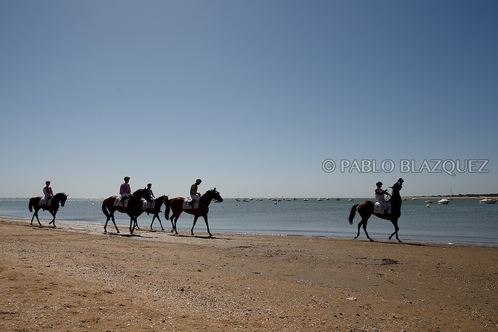 12/08/2016. Jockeys prepare for the start of the beach horse races on August 12, 2016 in Sanlucar de Barrameda, Cadiz province, Spain. Sanlucar de Barrameda yearly horse races traditional origin started with informal races of horse's owners delivering fish from the port to the markets. But the first formal races date back to 1845 and they are the second oldest in Spain, after Madrid. The horse races take place near the Guadalquivir river mouth during August