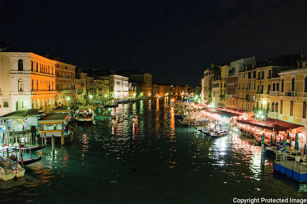 The Grand Canal, Venice, Italy at night.  Looking south from the Rialto Bridge, the canal, bright lights and bustling restaurants lend Venice a wonderful atmosphere.