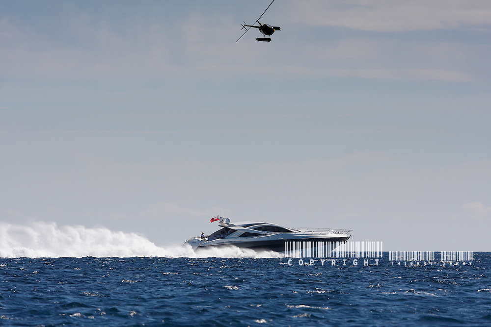 HELICOPTER AND MAXI MOTOR YACHT CRUISING OFFSHORE. SAINT-TROPEZ LIFESTYLE