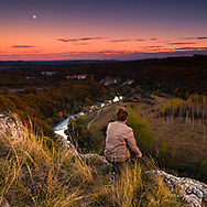 A Man sitting on the edge of a canyon