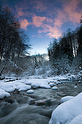 Pink clouds color the sky above Boardman Creek in the Central Cascades of Washington state on a winter evening.