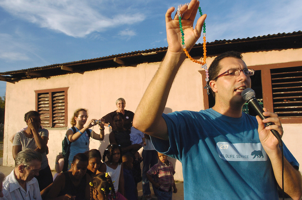 Fr. Oriol Regales displays a rosary during a gathering outside the chapel at El Rosario. Rosaries made by children from St. Mary Parish in Port Washington and distributed to children in El Rosario. Located in the Diocese of San Juan de la Maguana, Dominican Republic.  El Rosario is one of 28 communities that make up La Sagrada Familia (Holy Family) Parish, which is directed by priests of the Archdiocese of Milwaukee. The archdiocese celebrated the 25th anniversary of its relationship with La Sagrada Family in late October. Fr. Marti Colom, left, pastor, and four young girls, who are standing outside of the church, listen to Bishop Sklba. (Catholic Herald photo by Sam Lucero)<br />