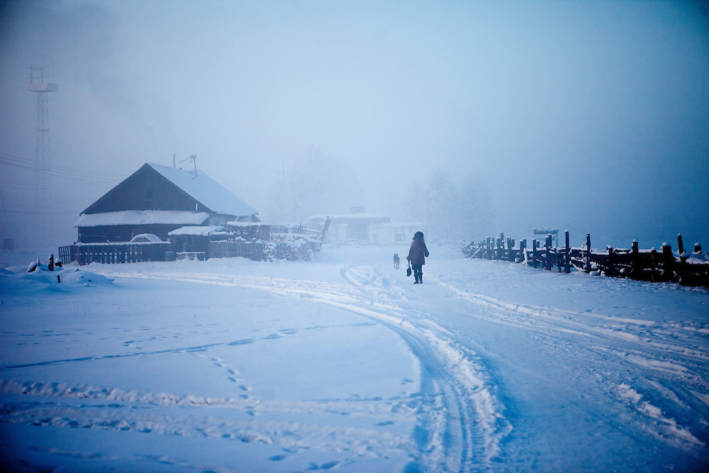 "A woman is walking her dog at ""The Pole of Cold"" in the village of Oymyakon - it is said that the lowest temperature ever here was -71.2°C. The area is extremely cold during the winter."