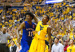 Jan 24, 2017; Morgantown, WV, USA; West Virginia Mountaineers guard Daxter Miles Jr. (4) shoots a three pointer over Kansas Jayhawks guard Josh Jackson (11) during the second half at WVU Coliseum. Mandatory Credit: Ben Queen-USA TODAY Sports