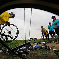 Rick Woodland (left) changes his tire while Janna Muir, Jennie Gordon (center) and Trudie Woodland look on Thursday morning during the fifth day of the Tour de Kota outside of Waconda.