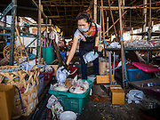 04 JANUARY 2016 - BANGKOK, THAILAND:        A worker packs up a housewares shop in Bang Chak Market on the last day the market was open. The market closed January 4, 2016. The Bang Chak Market serves the community around Sois 91-97 on Sukhumvit Road in the Bangkok suburbs. About half of the market has been torn down. Bangkok city authorities put up notices in late November that the market would be closed by January 1, 2016 and redevelopment would start shortly after that. Market vendors said condominiums are being built on the land.     PHOTO BY JACK KURTZ