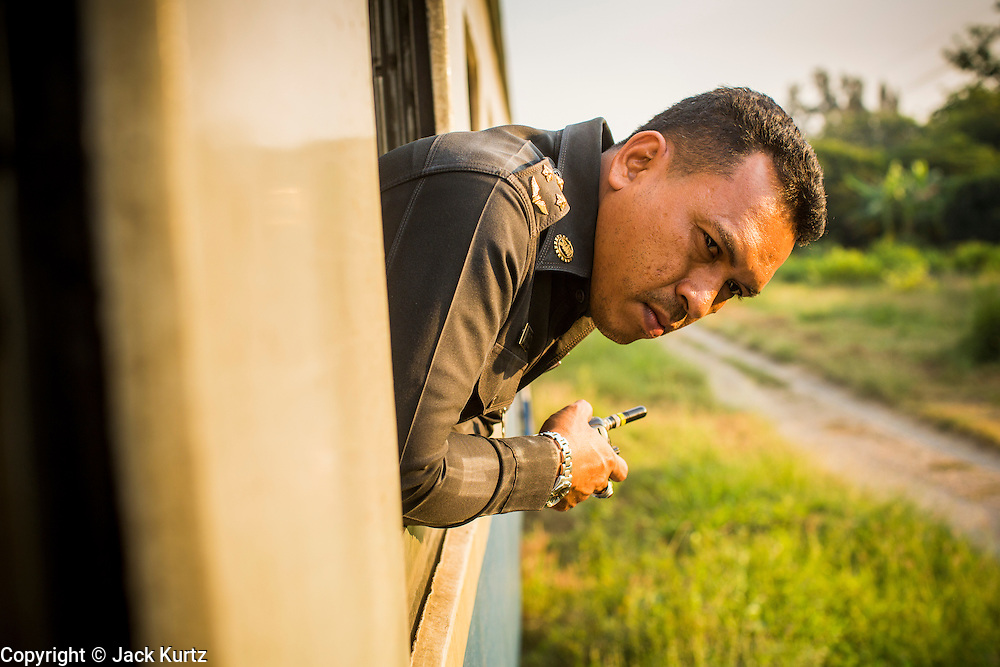07 JANUARY 2013 - KANCHANABURI, THAILAND:  A conductor looks out the window of the third class train between Kanchanaburi and Bangkok (Thonburi station) in Kanchanaburi, Thailand.  Thailand has a very advanced rail system and trains reach all parts of the country.    PHOTO BY JACK KURTZ