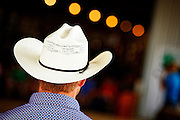 Cowboy wearing cowboy hat, walking away from camera, close-up, county fair, horse show, close-up, shallow depth of field