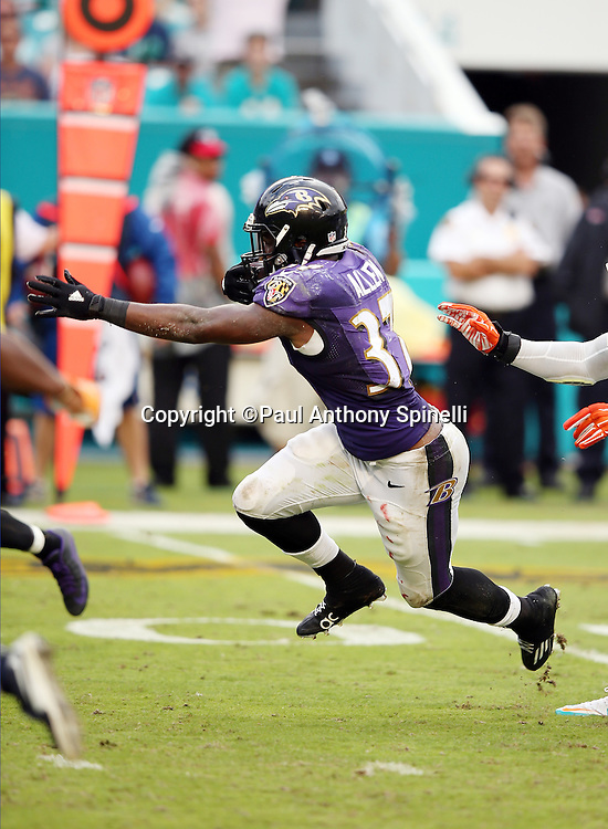 Baltimore Ravens running back Javorius Allen (37) runs the ball in the fourth quarter while being chased by Miami Dolphins middle linebacker Kelvin Sheppard (52) during the 2015 week 13 regular season NFL football game against the Miami Dolphins on Sunday, Dec. 6, 2015 in Miami Gardens, Fla. The Dolphins won the game 15-13. (©Paul Anthony Spinelli)