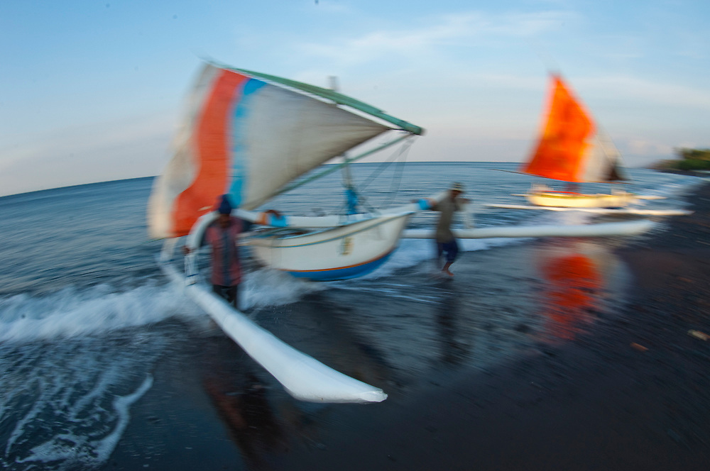 Fishermen in Tulamben, Bali, landing their jukungs on the beach in late afternoon. The jukung is the traditional fishing vessel in Bali, Indonesia. Image available as a premium quality aluminum print ready to hang.