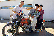 GOBI DESERT, MONGOLIA..09/03/2001.Bayanhongor (Bayankhongor). Youngsters with Motorbike..(Photo by Heimo Aga).
