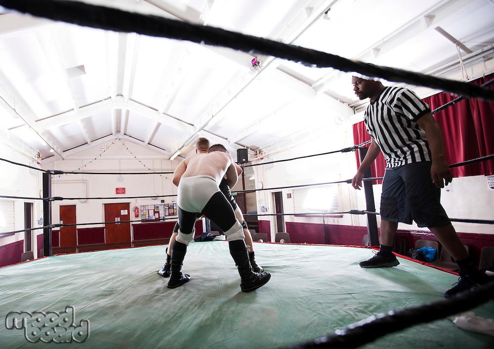 Full-length of wrestlers fighting in ring
