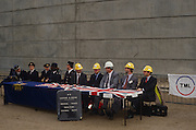 A theatrical joke about bureaucracy between French and British comedians at an event to mark the opening of the Channel Tunnel produces this quirky scene where each country's officials are seated at a long table, dressed in British flags, to symbolise the controls on human traffic that will soon pass through the tunnel beneath the sea between England and France, the first physical link between these two land masses since the Ice Age. Wearing smart uniforms, French immigration police and Gendarmes sit among British customs and immigration officials who, rather comically wear yellow hard hats because Health and Safety laws make the wearing of protective headgear compulsory on construction sites. A frontier control point notice stands for the benefit of viewers who might otherwise be guessing what is going on.