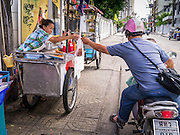 "04 OCTOBER 2012 - BANGKOK, THAILAND: A motorcyclist picks up a ""to go"" order from a street food stall on Sukhumvit Soi 22 in central Bangkok. Thailand in general, and Bangkok in particular, has a vibrant tradition of street food and ""eating on the run."" In recent years, Bangkok's street food has become something of an international landmark and is being written about in glossy travel magazines and in the pages of the New York Times.       PHOTO BY JACK KURTZ"