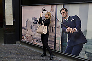 A lady pauses to take a picture of the nearby Lloyds Building next to a closed shop poster featuring a businessman wearing a blue suit - a favoured style and colour of menswear in the City of London, the capital's financial district - aka the Square Mile, on 29th August 2018, in London, England.