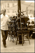 french waiter carring tray with chairs in outdoor cafe,sepia,verticle