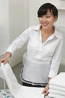 Female housekeeper looking away while folding white towel