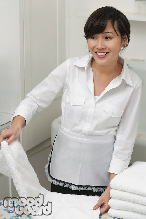 Female housekeeper looking away while folding white towel