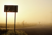 car on rural country road in the morning fog passing a sign with bullet holes shot in the sign