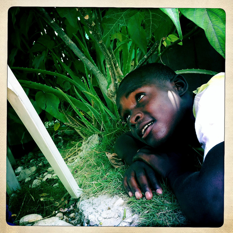 A boy lies in the bushes at the Corail camp on Thursday, April 5, 2012 in Port-au-Prince, Haiti.