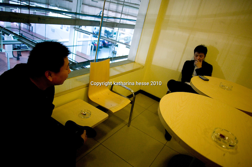 BEIJING, APRIL-22, 2010:   customers relax in the smoking room while waiting for their cars at the BMW dealership .
