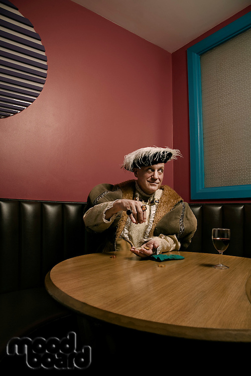King Henry VIII counting money at table in bar