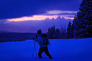 A man cross country skiing at dusk at Togwotee Pass, Bridger Teton National Forest in a overcast day in winter.  Grand Teton Range is in thebackground.  Model Released #0022010
