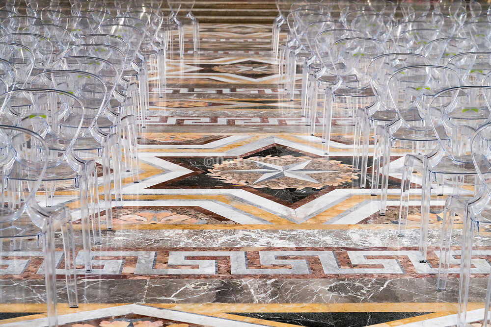 transparent plastic chairs on elegant marble floor in Palazzo Reale Caserta Italy